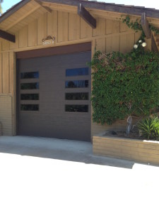 A brown flush garage door with tinted windows placed vertically